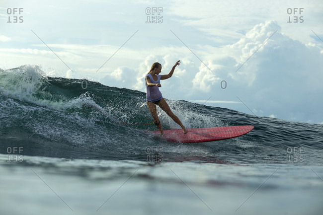 Female Surfer Keeps Her Balance While Surfing On Wave