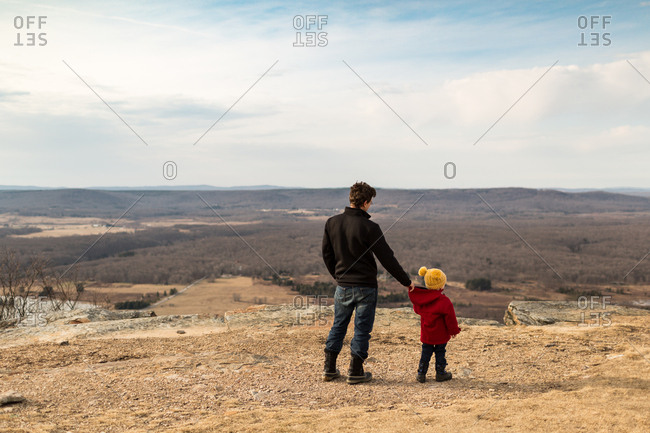 Father holding son's coat while walking on top of mountain