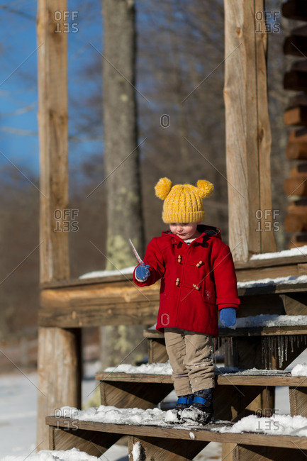 Toddler boy holding icicle on steps