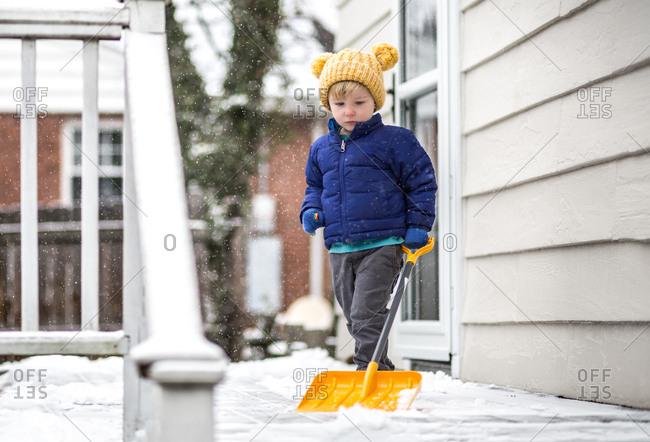 Toddler boy shoveling snow