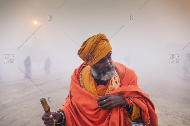 Allahabad, Uttar Pradesh, India - January 28, 2013: Man stopping to kneel and rest during Maha Kumbh Mela, the Hindu pilgrimage of faith