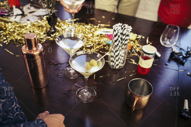 High angle view of stirrers and drinks with containers on wooden table during party
