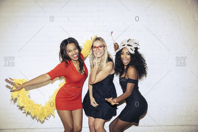 Portrait of sensuous women with props posing against wall during party