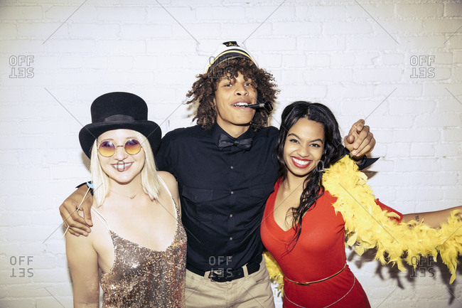 Portrait of young man standing with arms around women at party