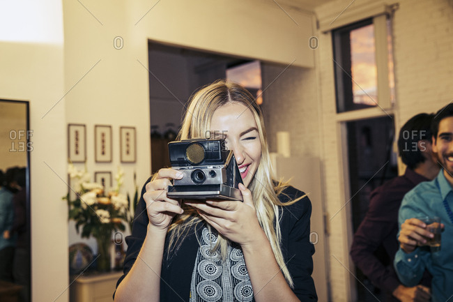 Happy young woman photographing through retro camera at party