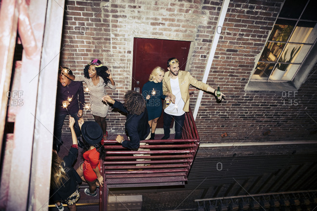 High angle view of Multi ethnic friends enjoying party on balcony at night