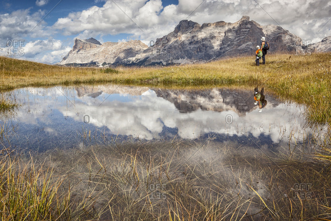Hikers at lake in Pralongia meadows, in background the Sasso della Croce mountain, Val Badia, Dolomites, South Tyrol, Italy