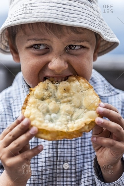 Hungry child eats Turtres, traditional ladin food, South Tyrol, Dolomites, Italy