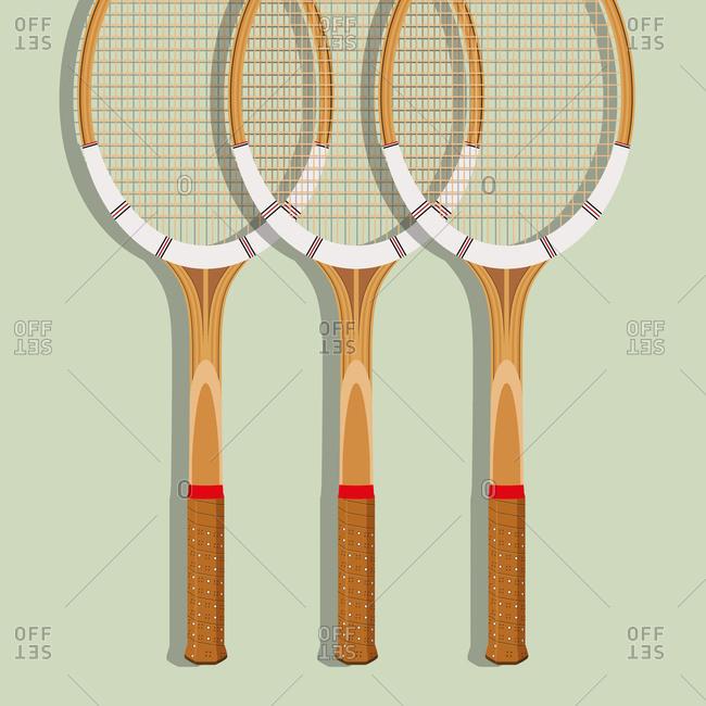 Three wooden tennis rackets on green background