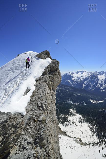 Female back-country skier ascending to Corno d Angolo, Cristallo Group, Dolomites, Veneto, Italy