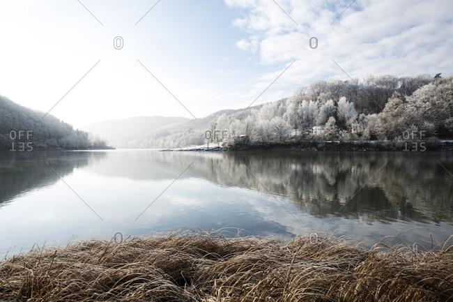 Reflection of a winter wonderland landscape in Lake Edersee, Lake Edersee, Hesse, Germany, Europe