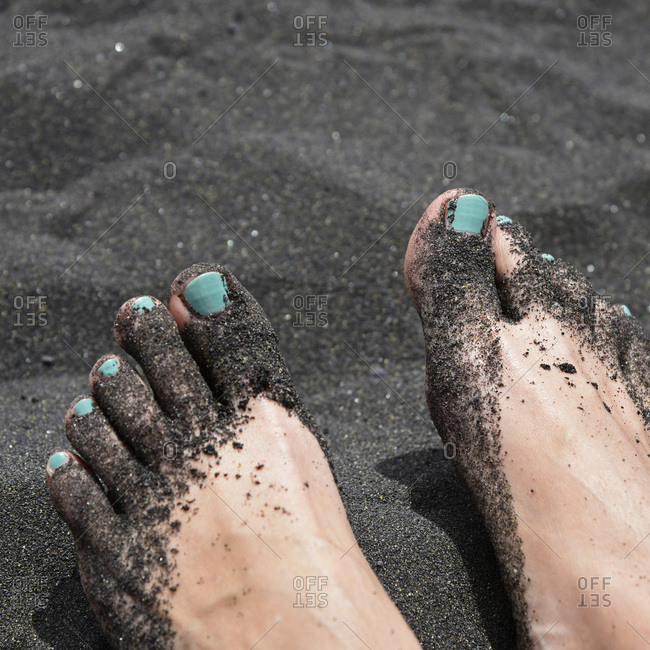 Feet with black sand, beach of Puerto Naos, La Palma, Canary Islands, Spain