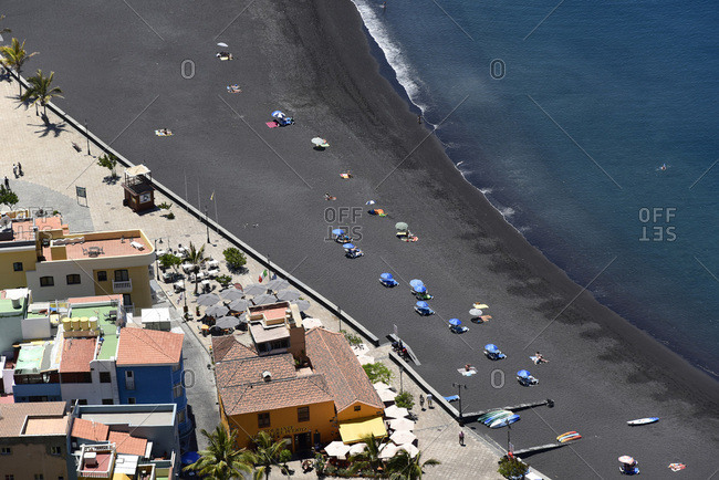 La Palma, Spain - June 11, 2015: Overhead view of town and beach goers with ocean waves meeting the black beach of Puerto de Tazacorte