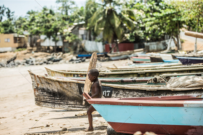 Sao Tome, Sao Tome and Principe - October 14, 2015: Little native boy carrying a piece of wood through a row of boats towards the beach