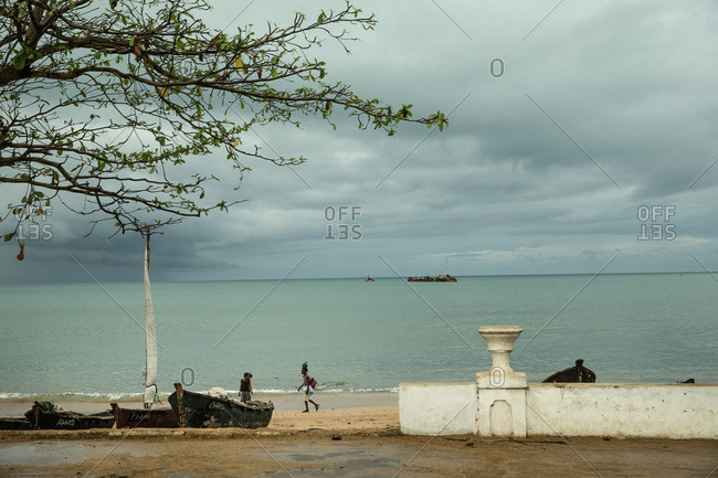 Sao Tome, Sao Tome and Principe - October 6, 2015: Two local girls walking past two simple fishing boats on the beach