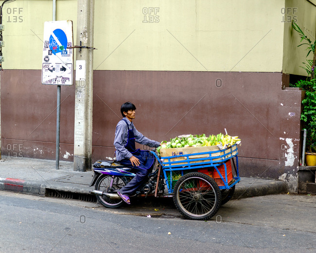 Bangkok, Thailand - March 6, 2015: Fruit vendor riding a tricycle on the street