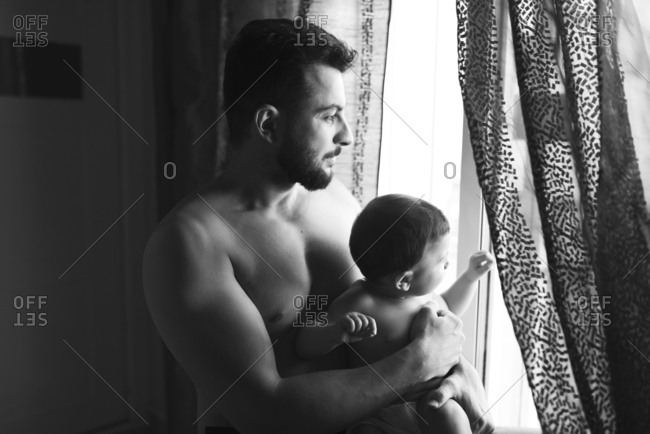 Father holding baby son in home bedroom