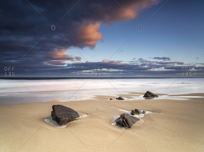 Coastal landscape with rocks on a beach.