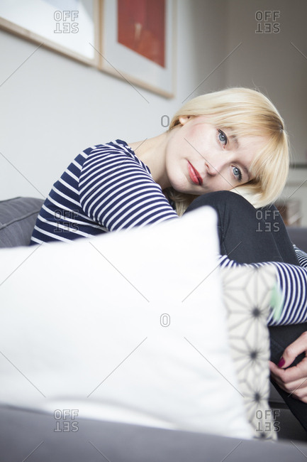 Beautiful woman curled up on the couch at home