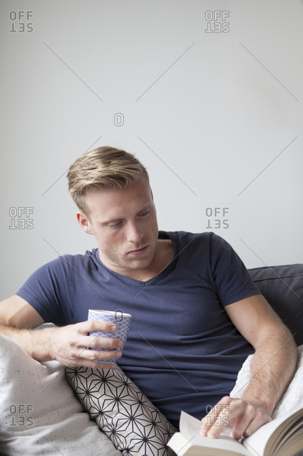 Young man reading a book at home and sipping tea