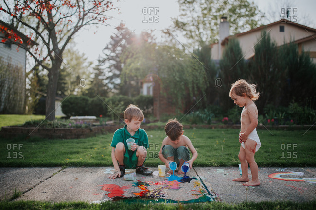 Three siblings playing with chalk paint on sidewalk