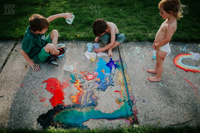 Kids playing with chalk paint on sidewalk