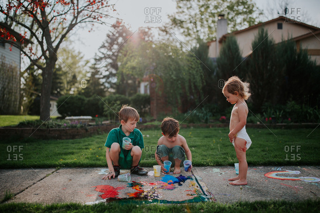 Siblings playing with chalk paint on sidewalk
