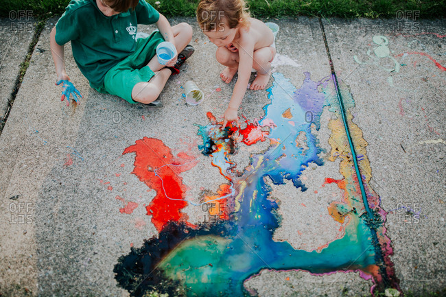Toddler and big brother playing with chalk paint on sidewalk