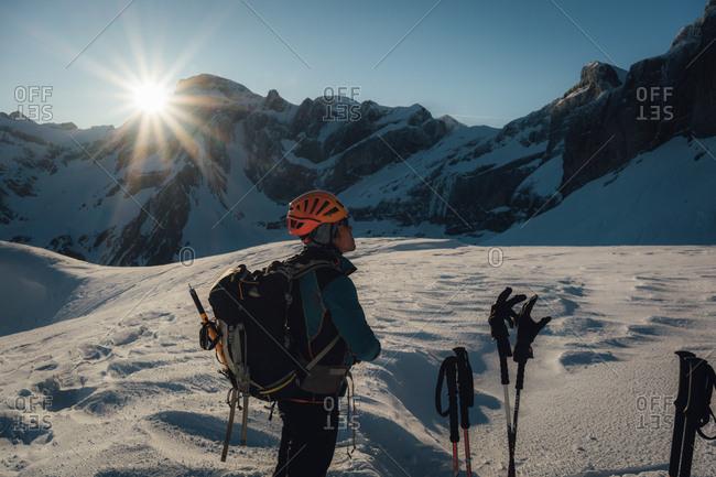 France - April 6, 2017: Ski mountaineer looks up in sunrise light