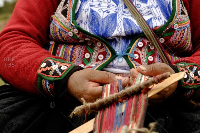 Quechua women preparing fibers to weave traditional Andean clothing in Peru.