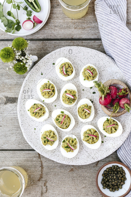 Avocado deviled eggs are served on farm table.