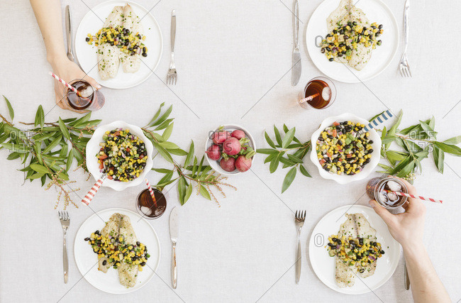 A summery (happy & bright) table setting with a portion of Baked Lime and Olive oil tilapia with black bean salsa served on each plate. (only glasses)