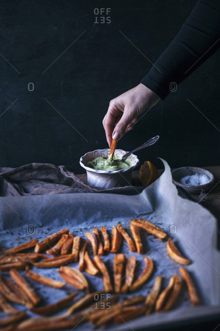Woman dipping oven baked sweet potatoes fries into avocado sauce