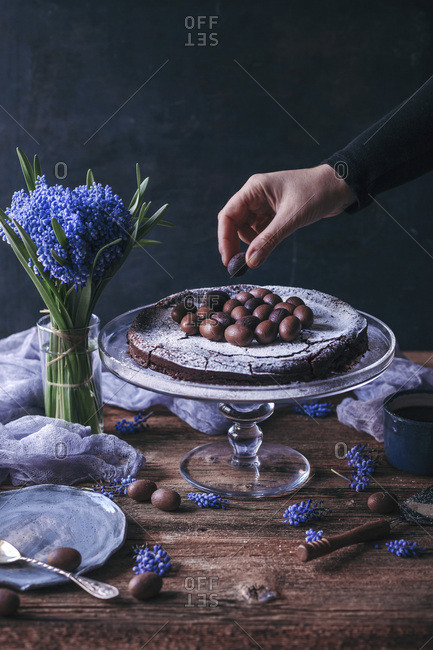 Woman putting chocolate eggs as decoration on top of Swedish chocolate cake on a cake stand