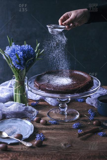 Woman sprinkling powdered sugar on top of Swedish chocolate cake on a cake stand