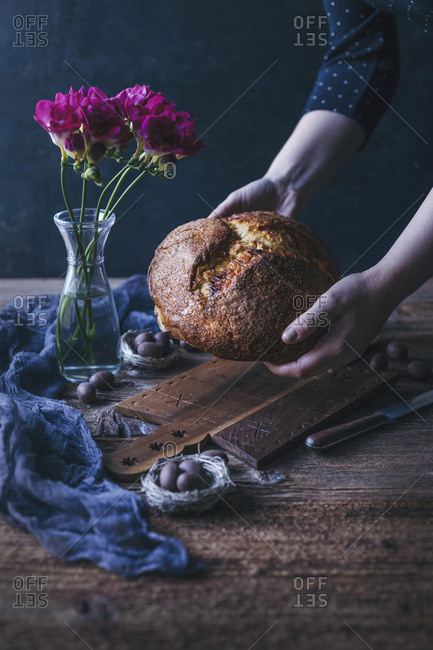 Woman holding a freshly baked sweet Easter bread in her hands
