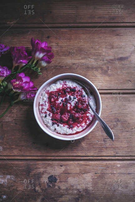 Porridge with raspberry sauce and cacao nibs in a bowl