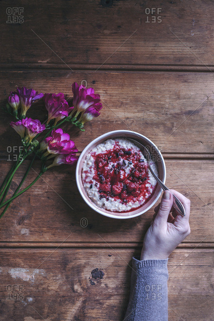 Woman eating porridge with raspberry sauce and cacao nibs in a bowl