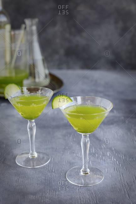Matcha Cucumber Spritzertini Winetail cocktail. Photographed from front view on a grey background.