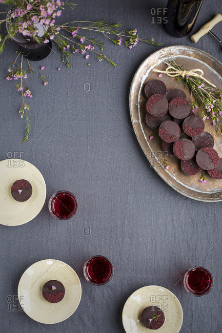 Marzipan Hibiscus Cups served on a copper tray with a dessert wine. Photographed on a grey table cloth.