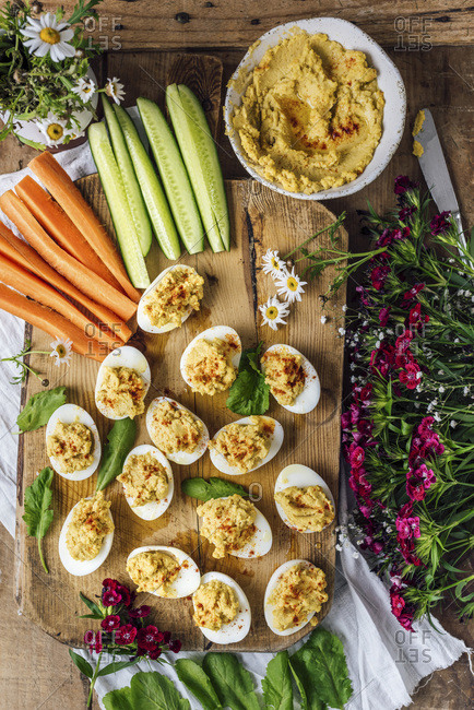 Hummus deviled eggs are served on a wooden board with cucumber and carrot sticks, arugula, and flowers. A bowl of hummus accompany.