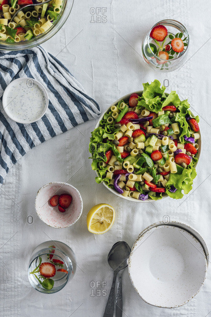 Strawberry Pasta Salad with herbs and cucumber in a bowl and accompanied by two glass of flavored water and bowls.