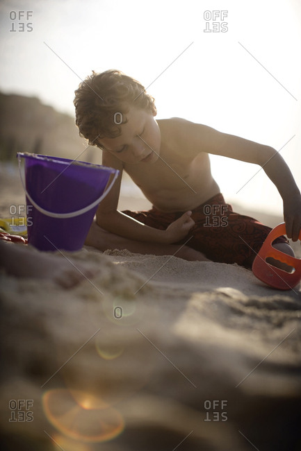 Young boy playing in the sand at the beach
