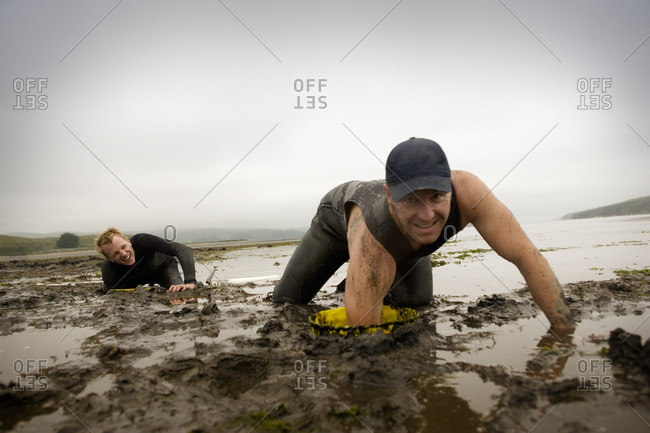 Two men digging for shellfish in the sand