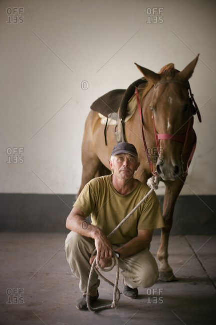 Man crouching next to his horse