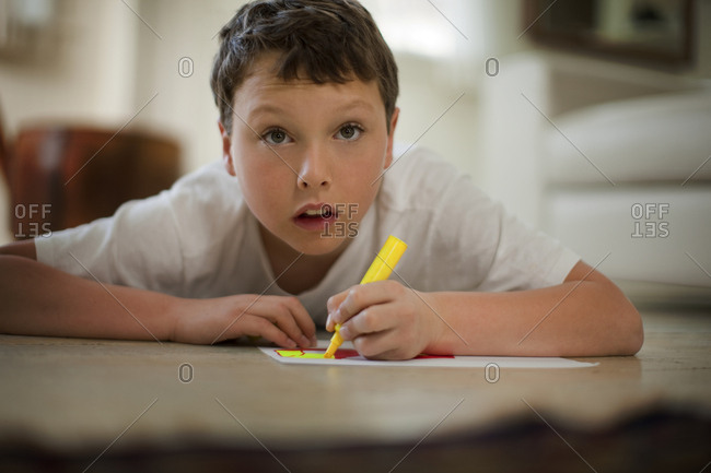 Young boy writing with a highlighter pen