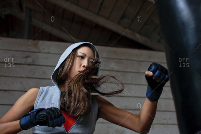 Young woman boxing a punching bag