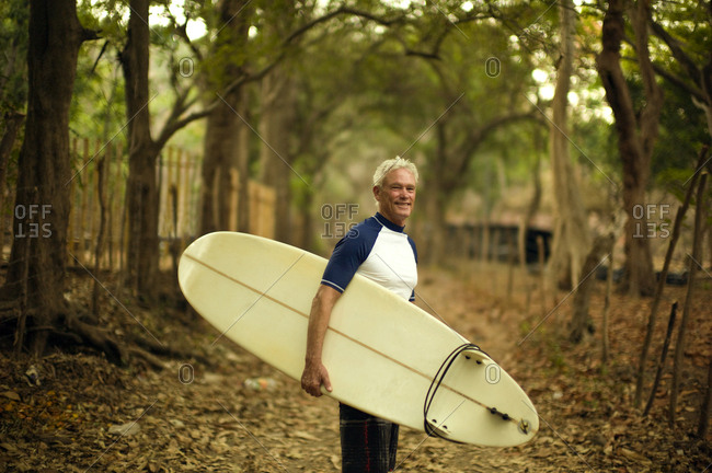 Man carrying his surfboard on a wooded path