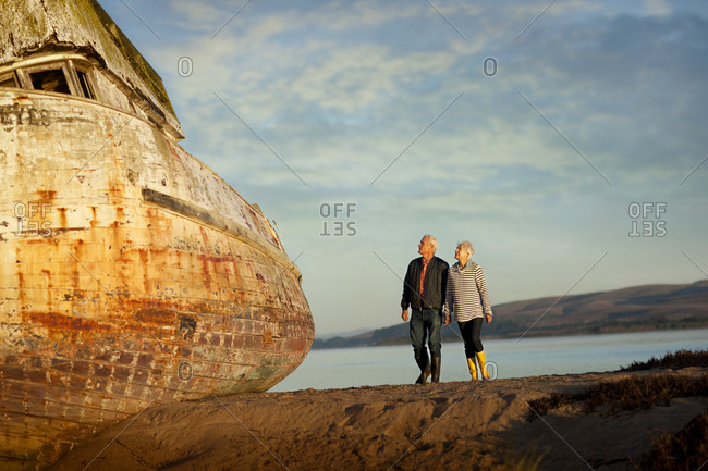 Couple looking at a shipwreck on the beach