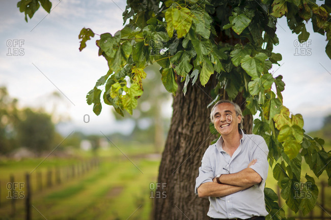 Smiling senior man standing under a tree